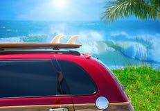 Röd träig bil med surfingbrädan på stora vågor för strandw Arkivbild