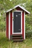 Röd träkabin för WC i den lantliga wc:n för skog Arkivfoto