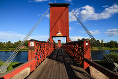Röd träupphängningbro över floden i Dala Floda Sweeden royaltyfri foto