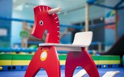 Röd trävagga häst i en inomhus lekplats arkivbild