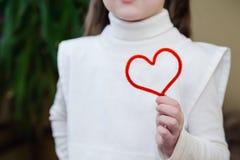 Röd tråd i form av hjärta i händerna av en flicka royaltyfri fotografi