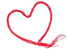 Röd tråd med hjärtatecknet som isoleras på vit bakgrund royaltyfri foto