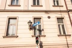 Röd trafikljus för gångare och ett tecken för riktningsvägpil för bilar på övergångsstället på gatan i stadsslutet upp w royaltyfri bild