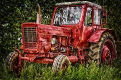 Röd traktor för gammal otvungenhet i natur arkivfoton