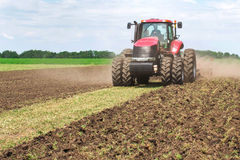 Röd traktor för modern tech som plogar ett grönt jordbruks- fält i vår på lantgården Skördearbetaresåddvete Arkivbild