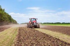 Röd traktor för modern tech som plogar ett grönt jordbruks- fält i vår på lantgården Skördearbetaresåddvete Arkivfoton