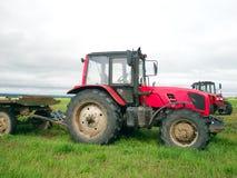 Röd traktor i fältet royaltyfri fotografi