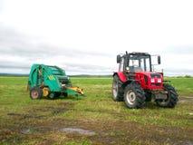Röd traktor i fältet arkivfoton