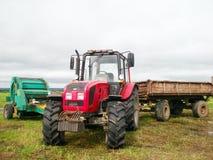 Röd traktor i fältet royaltyfria foton