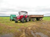 Röd traktor i fältet arkivbild