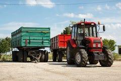 Röd traktor med släpet och gräsplansläpet bara, parkerat på en gårdsplan mot blå himmel Royaltyfri Fotografi