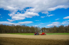 Röd traktor på ett fält Royaltyfri Bild