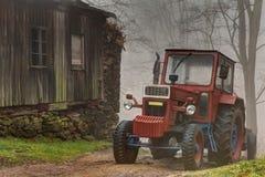 Röd traktor vid träbyggnaden royaltyfri fotografi