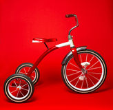 Röd trehjuling för tappning på en ljus röd bakgrund Arkivbild