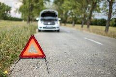Röd triangel som varnar de andra väganvändarena om en skadad bil Royaltyfri Fotografi