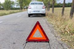 Röd triangel som varnar de andra väganvändarena om en skadad bil Arkivbilder