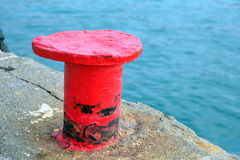 Röd tumme på stenpir royaltyfri bild