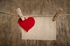 Röd tyghjärta med arket av pappers- hänga på klädstrecket Royaltyfri Fotografi