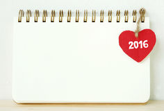 Röd tyghjärta med ord som 2016 hänger på den tomma anmärkningsboken Arkivbilder