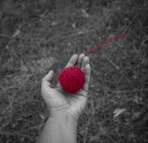 Röd ull clew i den mänskliga handen, bästa sikt arkivfoto