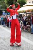 Röd underhållare på styltor och stora kängor Royaltyfri Fotografi