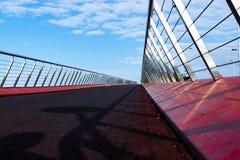 Röd upphängningbro med en blå himmel royaltyfri foto