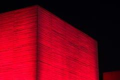 Röd upplyst betongvägg av brutalistbyggnad på natten Royaltyfria Foton