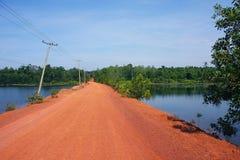 Röd väg till vattenfallet i Cambodja Arkivfoto