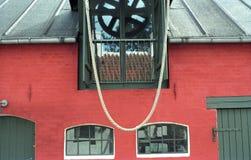 Röd vägg för tegelsten och gröna fönster Arkivfoton