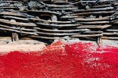 Röd vägg med det vide- staketet med jord Arkivbilder