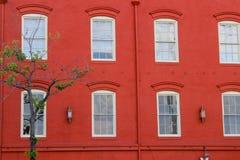 Röd vägg med fönster och det gröna trädet Royaltyfri Foto
