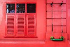 Röd vägg och fönster med grön gunga Arkivbild