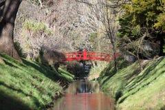 Röd välvd bro över ström i botaniska trädgårdar Royaltyfria Foton