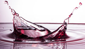 Röd vätskevattenfärgstänk med droppar Arkivfoto