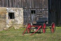 Röd vagn och ladugård Arkivfoto