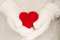Röd valentindaghjärta i händer med tumvanten arkivfoton