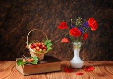 Röd vallmo i en vas och körsbär Arkivbild