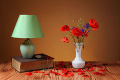 Röd vallmo i en vas- och tabelllampa Arkivbilder