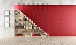Röd vardagsrum med den trätrappuppgången och bokhyllan Arkivfoton