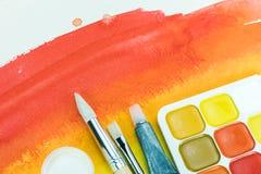 Röd vattenfärgtextur med färgpaletten och den olika målarpenseln Arkivfoto