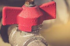 Röd vattenkran och rör/kran med porten för vatten close upp arkivfoto