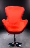 Röd velourplats på detpläterade stålbenet i studion på en svart bakgrund Bekväm röd kontorsstol Arkivbild