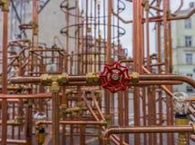 Röd ventil på kopparrörkonstruktion i utomhus- Arkivfoto