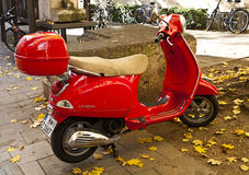 Röd Vespa som parkeras på trottoargatan Fotografering för Bildbyråer
