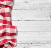 Röd vikt bordduk över den vita trätabellen Royaltyfri Foto