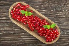 Röd vinbär i en träplatta på en träbakgrund Top beskådar Arkivfoto
