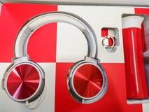 Röd-vit hörlurar, hörlurar som en gåva, mångfärgad musik royaltyfria foton