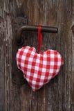 Röd vit kontrollerade hjärta som hänger på en gammal dörr arkivbild