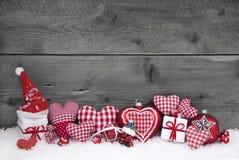 Röd vit kontrollerade julgarnering på grå träbakgrund Royaltyfri Foto