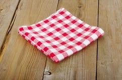 Röd-vit rutig bordduk i en trätabell Arkivbild